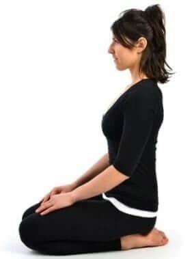 vajrasana-mulher-roupa-preta-fundo-branco